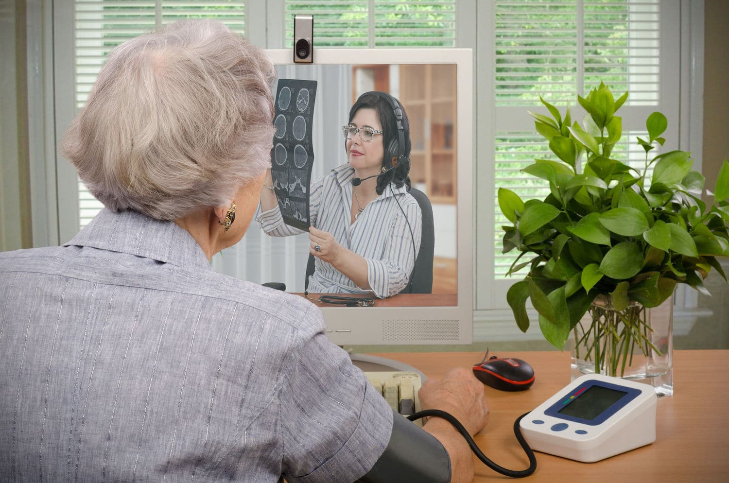 Telehealth kiosk - retired woman communicating with doctor through telehealth kiosk